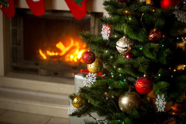 暖炉をバックにクリスマスツリーが飾られてる画像