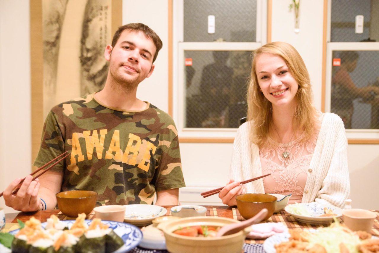 外国人の男女が日本食を食べている画像