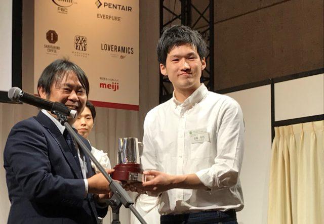 金藤さんに株式会社丸山珈琲代表取締役社長の丸山さんがトロフィーを渡している写真