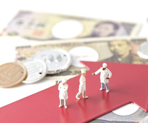 現金と赤い矢印のうえにコックさんの人形が立っている画像