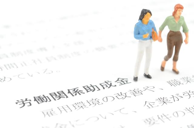 男女のフィギュアが労働関係助成金と書かれた紙の上に立っている