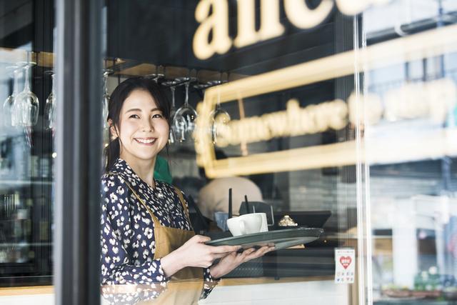 飲食店で働く黒いブラウスを着た女性が微笑んでいる