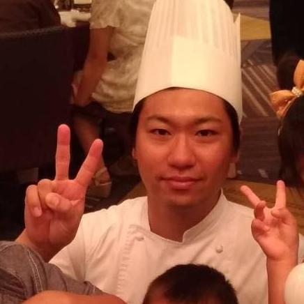 コックコート姿でピースをしている細田 隆広さんの写真