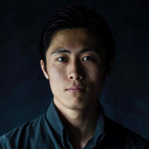 紺色シャツに黒背景の松島 佑季さんの写真