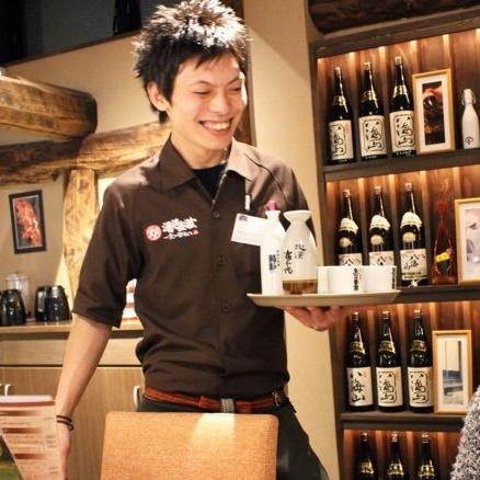 お酒をお盆に乗せて運んでいる関 智也さんの写真