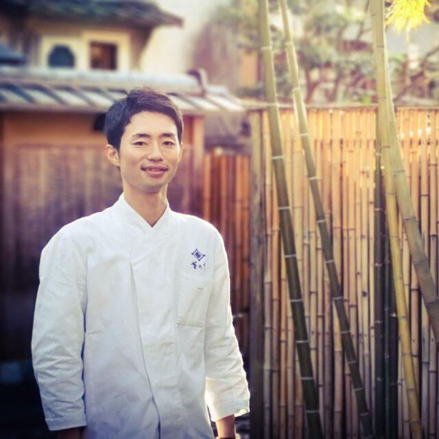 京都の料亭「菊乃井」の前でコック服を着て笑顔で立っている成田陽平さん