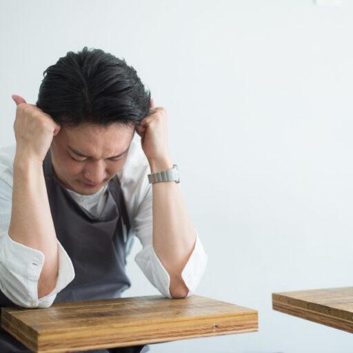 テーブルに肘をつき頭を抱える男性の写真