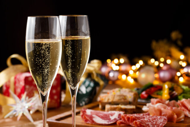 シャンパンとサラミなどの乗った気の皿のムーディーな写真