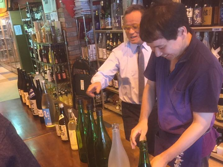 「ごとう屋」店内での勉強会で、お酒の瓶を手に講習する後藤社長