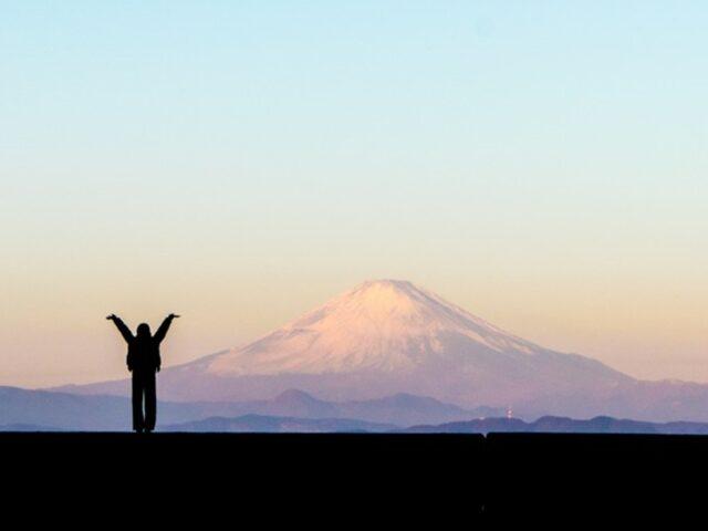 富士山をバックに両手をあげている女性の写真