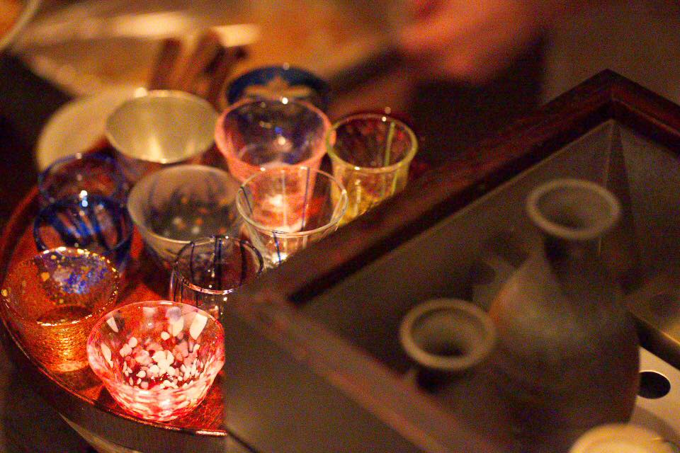 日本酒の徳利や、色も形もさまざまなおちょこが並んでいる写真