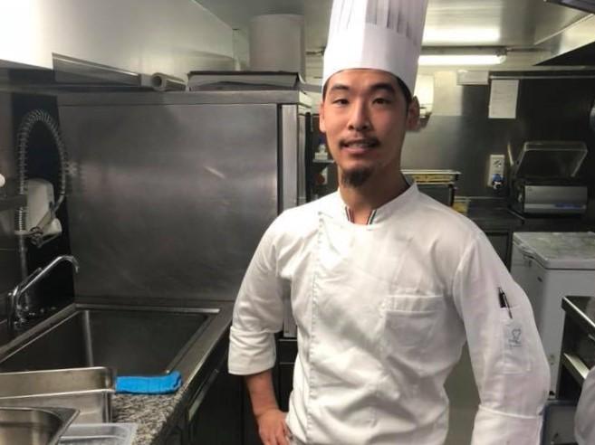 厨房の中でコック服を着てポーズを取る吉川 朴(よしかわ ほお)さん
