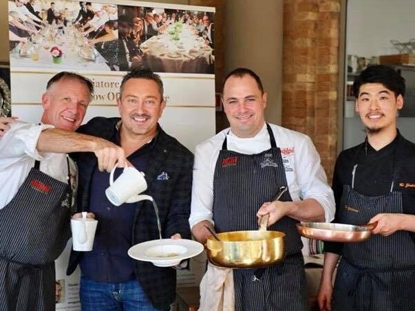 イタリアのレストラン内で3名のイタリア人料理人と集合写真に写る吉川さん