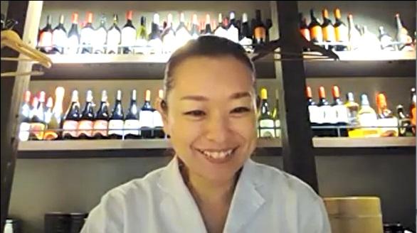 笑顔の鈴木さんの後ろにたくさんのお酒のボトルが並んでいる写真