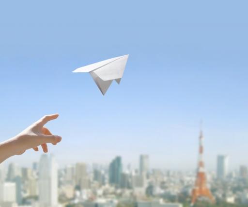 青空に向かって紙飛行機を飛ばしている女性の手の写真