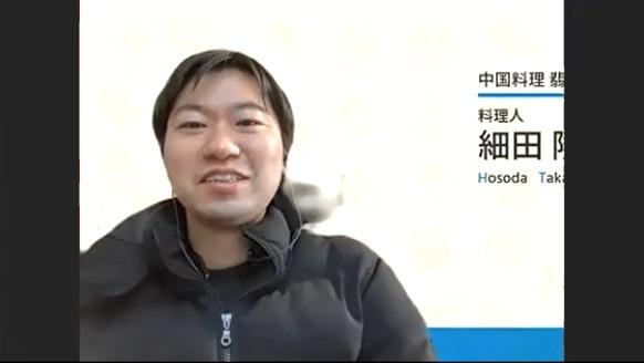少し背筋を伸ばして話す細田さんの写真