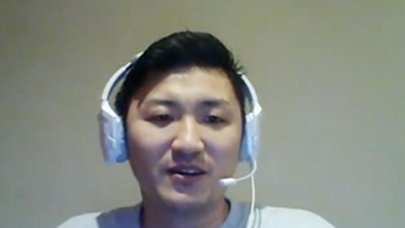 白いヘッドホンを付けて話をする藤井さんの写真