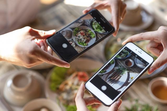 スマートフォンで料理の写真を撮影している様子