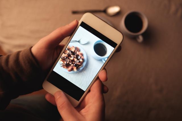 スマートフォン内で表示されている、チョコレートがかかったワッフルと、白いカップに注がれたコーヒーのイメージ写真