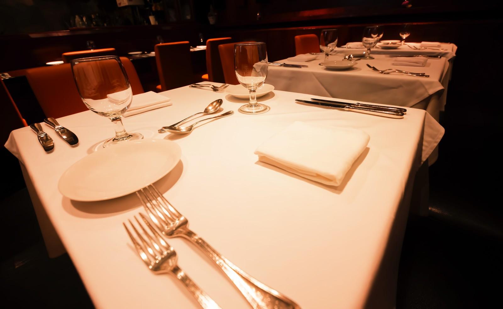 白いテーブルクロスが敷かれ、フォークやナイフ、お皿がきれいに並べられているレストラン店内のイメージ画像