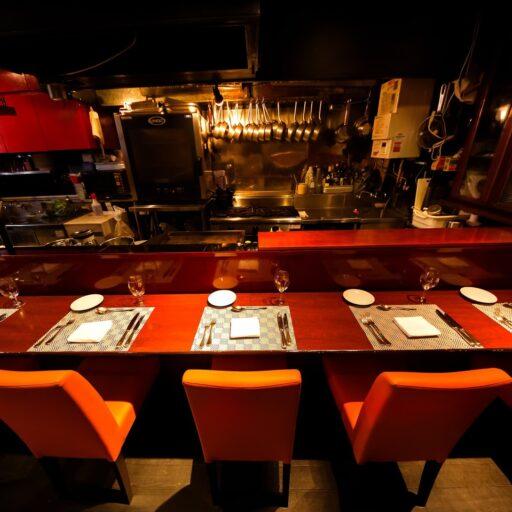 カウンターテーブル越しに厨房の様子を見ながら食事を楽しめるレストランのイメージ画像