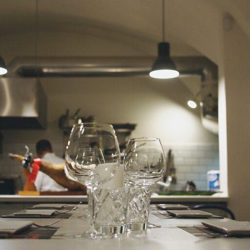 厨房の様子も楽しめるレストランのイメージ写真。テーブルには大小異なるワイングラスが置かれている