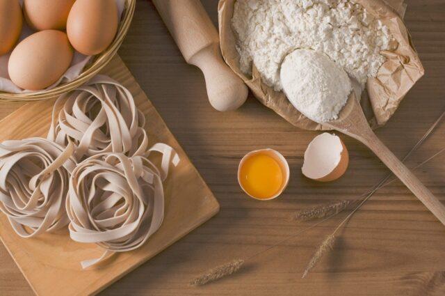 テーブルの上に、パスタや卵、小麦粉などが雑多に置かれている写真
