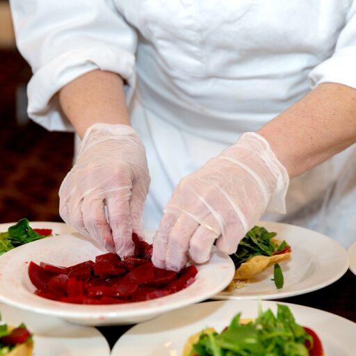 洋食の料理人がお皿に料理を盛り付けているイメージ画像