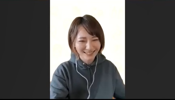 グレーのパーカーにイヤホンを付けた笑顔の加藤さんの写真