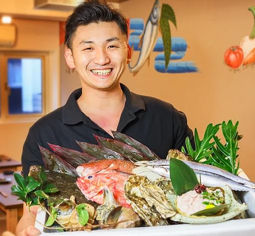 「和酒・旬菜・心 ひょうきん顔」のオーナー藤井さんが箱に入った魚介類を抱えている写真