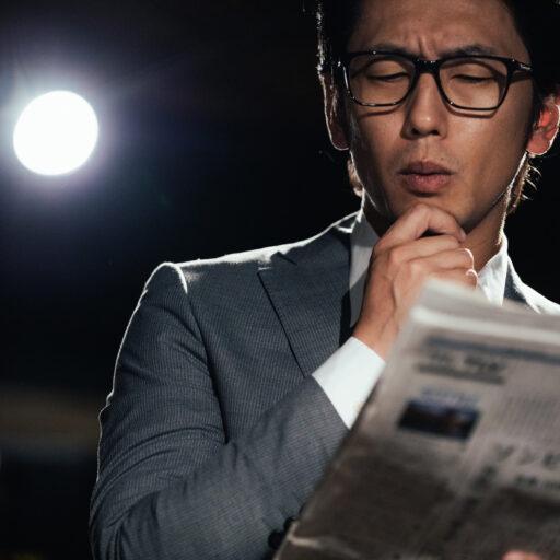 新聞を手に情報収集をするスーツ姿の男性の写真