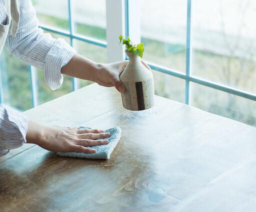 テーブルを清潔なダスターで拭き、衛星対策を行う飲食店の女性スタッフ