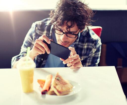 料理の写真を撮る男性の画像