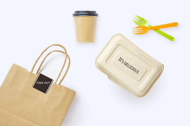 テイクアウト用の紙袋や容器、フォーク、紙コップの写真
