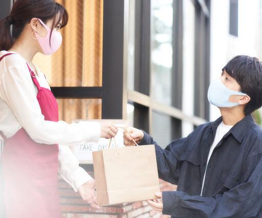 飲食店の女性スタッフが、モバイルオーダーで注文した男性のお客さんに商品の受け渡しを行っている写真