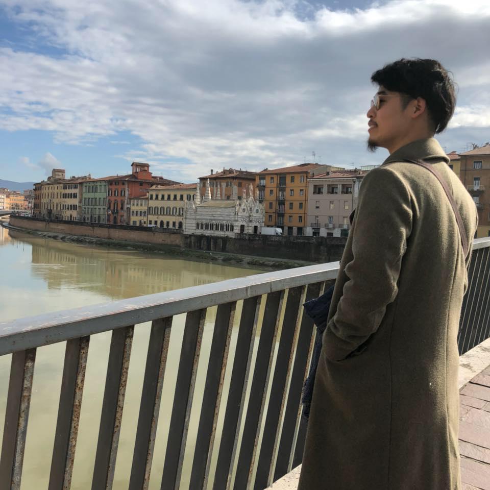 川の流れを眺めるカーキ色のコート姿の吉川さんの後ろ姿