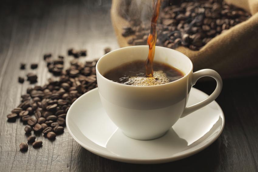 イメージ画像:コーヒー豆が散らばったテーブルの上で淹れたてのコーヒーをカップに注ぐ写真