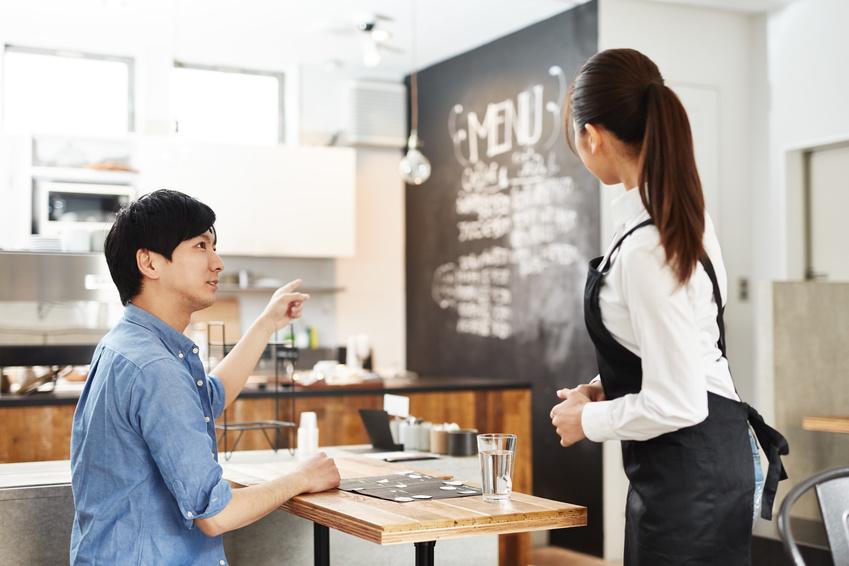 イメージ画像:カフェの店内で青いシャツの男性客が、白シャツ・黒いエプロンの女性スタッフにおすすめメニューを聞いている写真