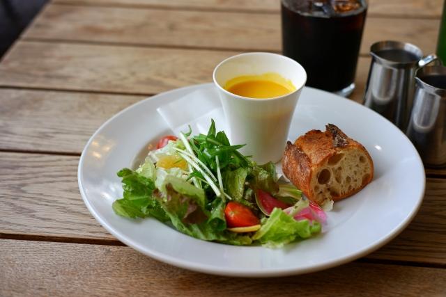 イメージ写真:木のテーブルの上にある白いお皿に盛り付けられたサラダとパン、スープ