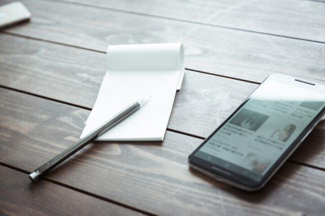 イメージ写真:スマートフォンとメモ帳の写真