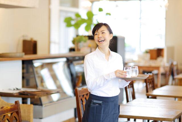 イメージ写真:カフェの店内でトレイを手に笑顔の女性スタッフ