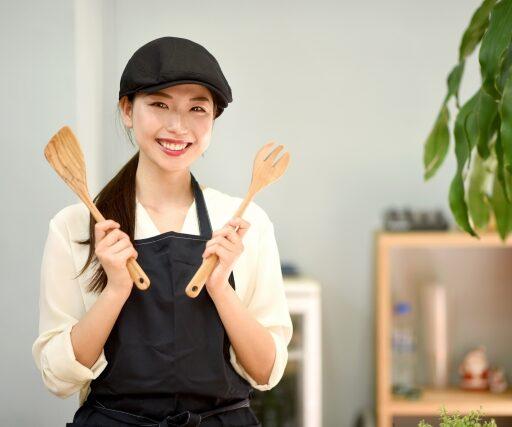イメージ写真:黒いエプロン、黒いキャップをかぶった女性スタッフが木の調理器具を手にカメラ目線の写真