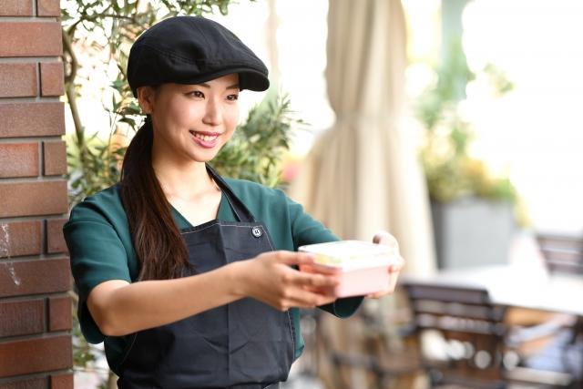 イメージ写真:カフェ店内でお客様に商品を提供する女性スタッフ
