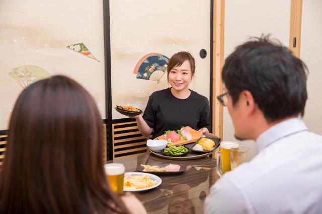 イメージ写真:居酒屋のお座敷でお客様に料理を提供する女性スタッフ