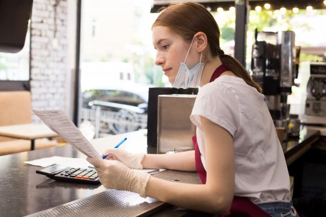 イメージ写真:マスクなど感染対策を行った店内で、書類に目を通す外国人女性