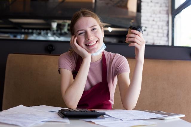イメージ写真:マスクをつけた外国人女性が、コーヒーカップを手にカメラ目線で笑顔の写真