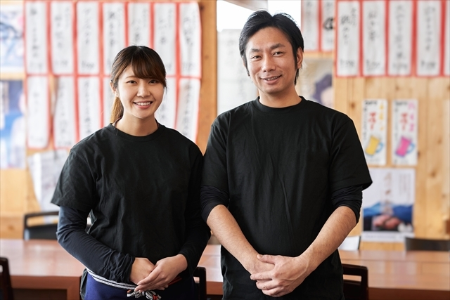 イメージ写真:居酒屋の店内で黒いTシャツを着た男女二人の集合写真