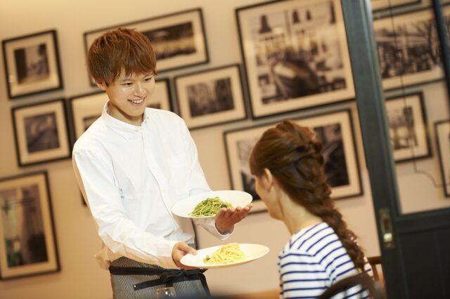 イメージ写真:レストランでの接客風景。女性スタッフがお客様にパスタを提供している