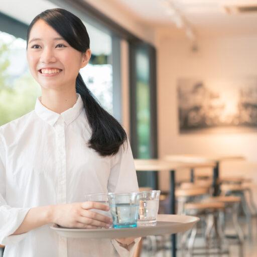 イメージ画像:カフェの店内でトレイにグラスを持ち笑顔の女性スタッフ