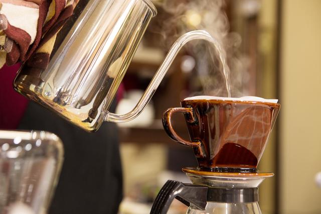 イメージ写真:コーヒーメーカーにお湯を注ぎコーヒーを抽出している写真